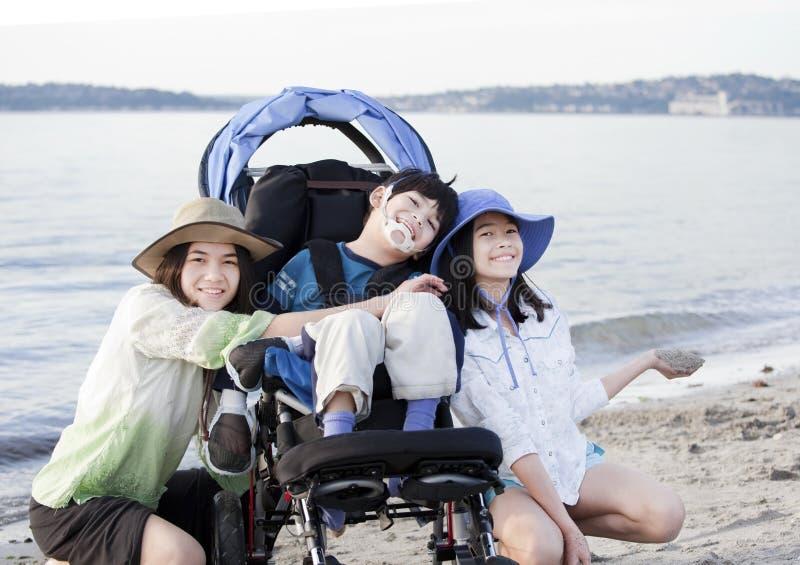 Zusters die gehandicapte broer op strand behandelen stock foto