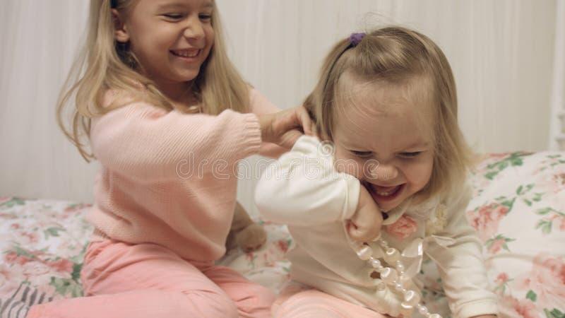 Zusters die met parels spelen die op een laag zitten stock afbeelding