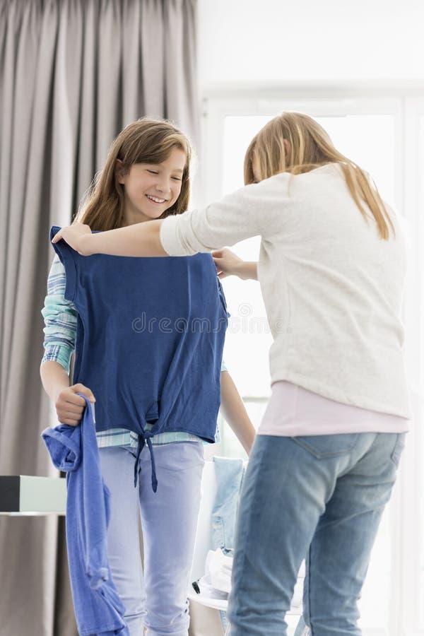 Zusters die op kleren thuis proberen stock foto