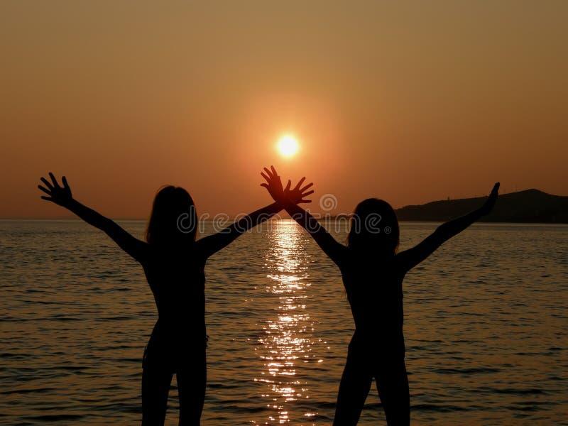 Zusters met open wapens in zonsondergang stock afbeeldingen