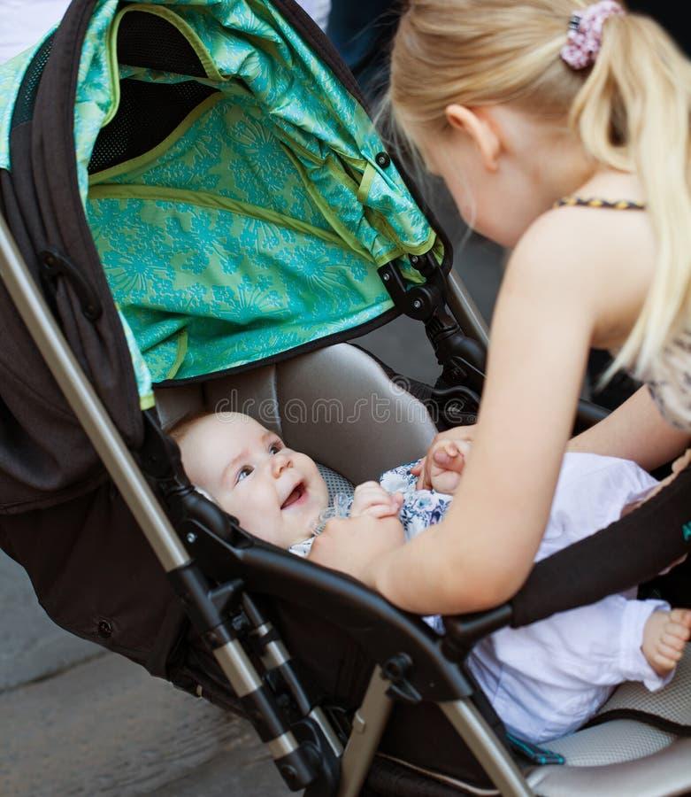 zusters Weinig babymeisje die aan haar zuster in openlucht glimlachen royalty-vrije stock afbeeldingen