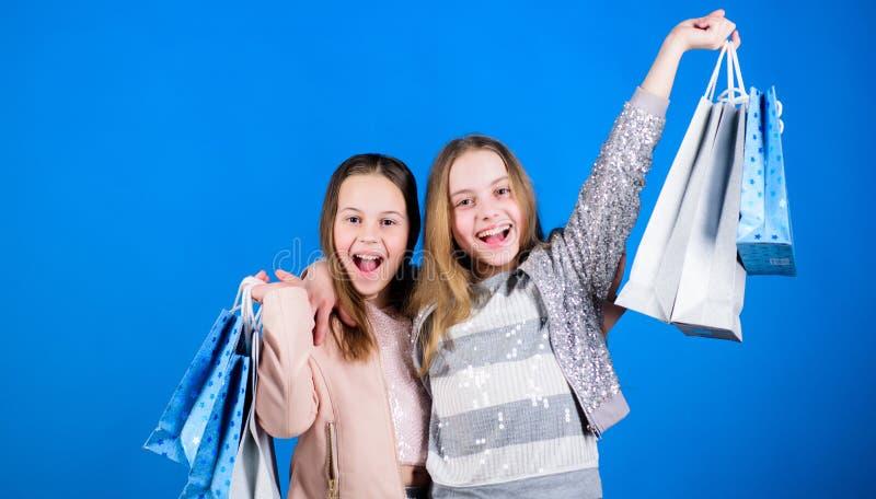 Zusterschap en familie besparingen op aankopen Verkoop en Kortingen jong geitjemanier Kleine meisjes met het winkelen zakken gelu stock foto's