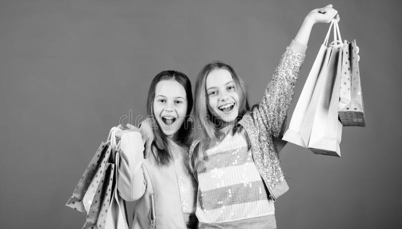 Zusterschap en familie besparingen op aankopen Verkoop en Kortingen jong geitjemanier Kleine meisjes met het winkelen zakken gelu stock afbeeldingen