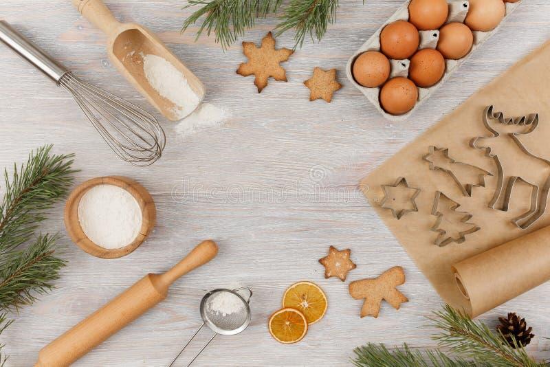 Zutaten und Küchenutensilien zum Kochen von Weihnachtsgebäck auf hellen Holztischen Mehl, Eier, Walzen, Stecker lizenzfreie stockfotografie