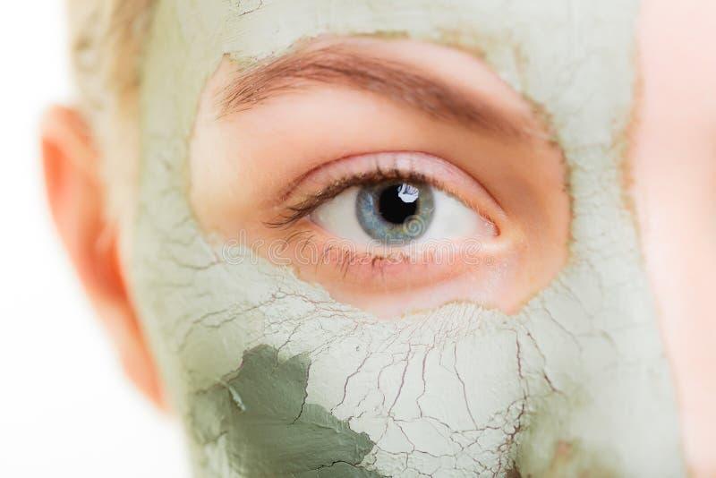 Zutreffen des transparenten Lacks Frau in der Lehmschlammmaske auf Gesicht schönheit lizenzfreie stockbilder