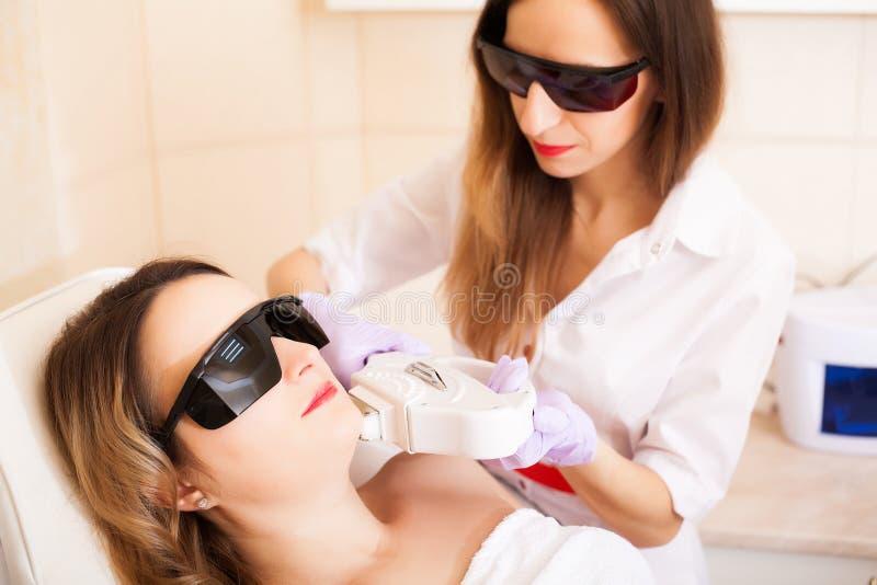 Zutreffen des transparenten Lacks Frau, die Laser-epilation Behandlung auf ihrem Gesicht empfängt lizenzfreie stockfotos
