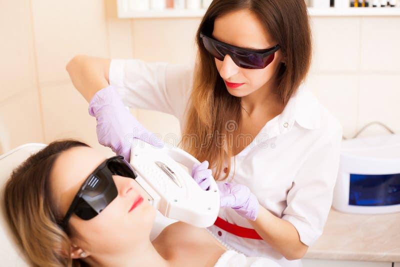 Zutreffen des transparenten Lacks Frau, die Laser-epilation Behandlung auf ihrem Gesicht empfängt lizenzfreie stockbilder