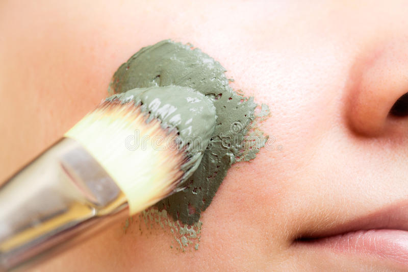 Zutreffen des transparenten Lacks Frau, die Lehmschlammmaske auf Gesicht anwendet stockbild