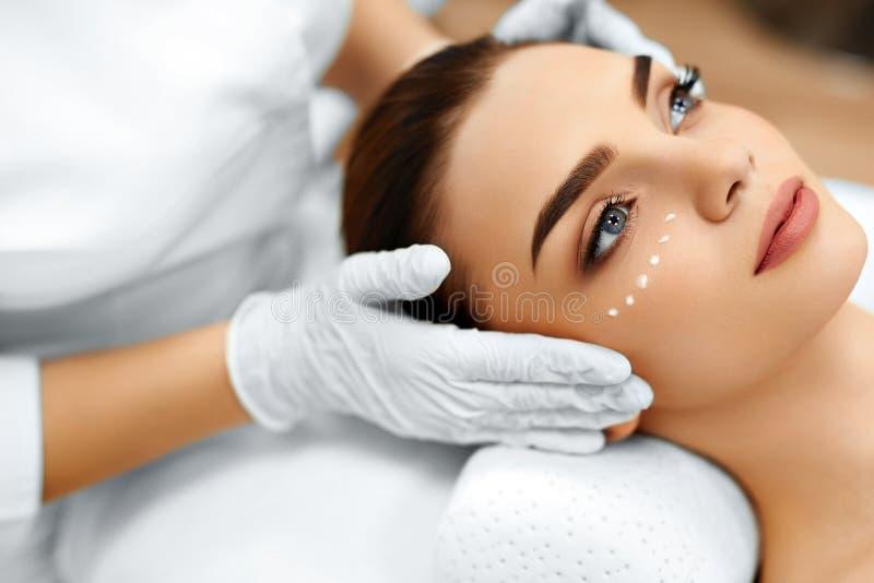 Zutreffen des transparenten Lacks Kosmetische Creme auf dem Gesicht der Frau Lächelnde junge Frau mit dem Daumen oben stockbild