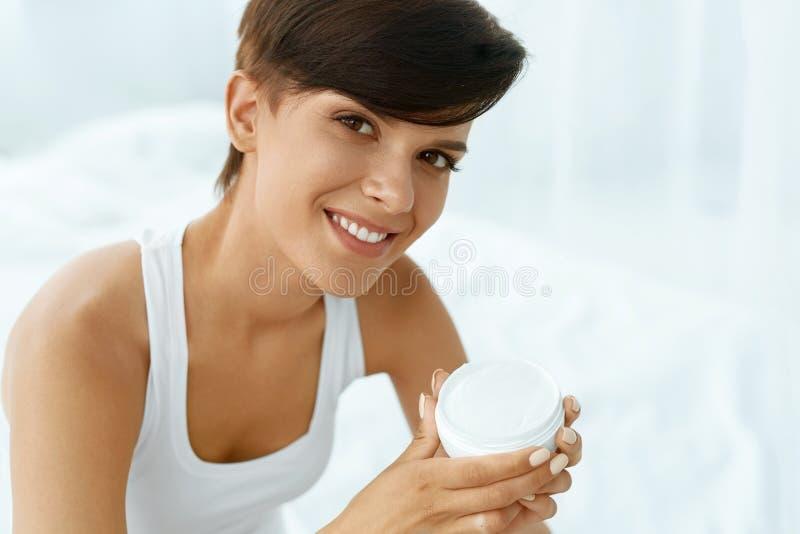 Zutreffen des transparenten Lacks Schöne glückliche Frau, die Gesichts-Creme, Lotion hält stockfotos