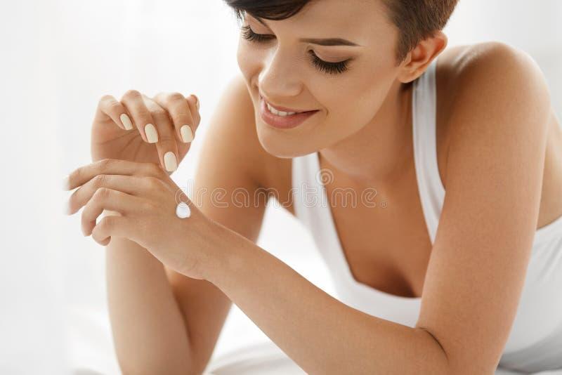 Zutreffen des transparenten Lacks Schöne glückliche Frau mit Handcreme, Lotion an Hand lizenzfreie stockbilder