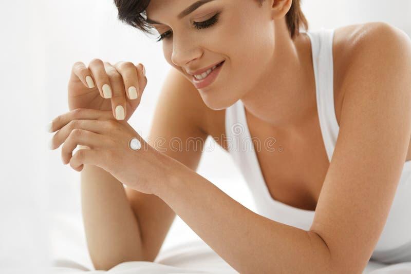 Zutreffen des transparenten Lacks Schöne glückliche Frau mit Handcreme, Lotion an Hand stockbild