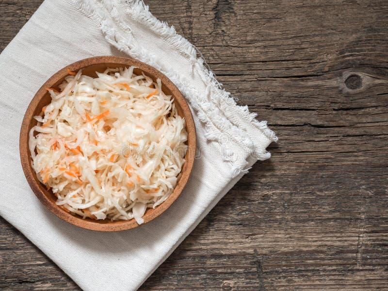 zuurkool Vergiste kool in een bruine kleiplaat op een houten lijst Gezond vegetarisch voedsel en beste natuurlijke probiotic stock afbeelding