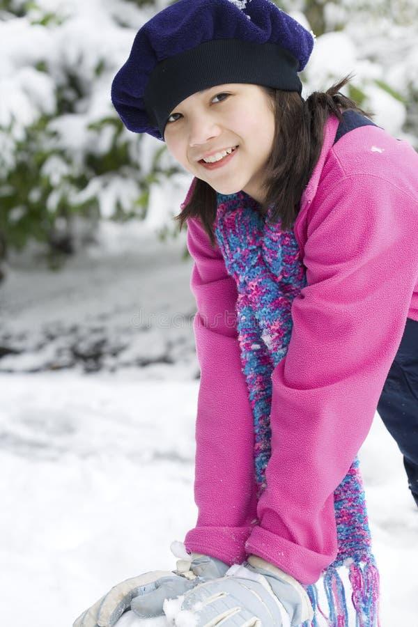 Zwölf Einjahresmädchen, das im Schnee spielt stockfotografie