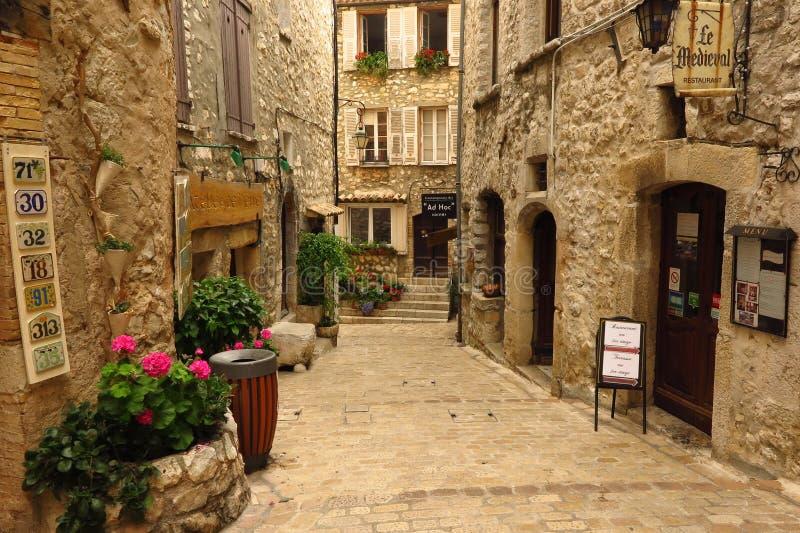 Zwęża się wykładającą ulicę w średniowiecznej wiosce Tourrettes-sur-Loup, Provence, Francja fotografia royalty free