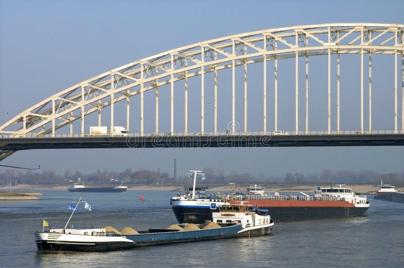 Zwaar verschepend verkeer op rivier Waal en Waalbrug stock afbeeldingen