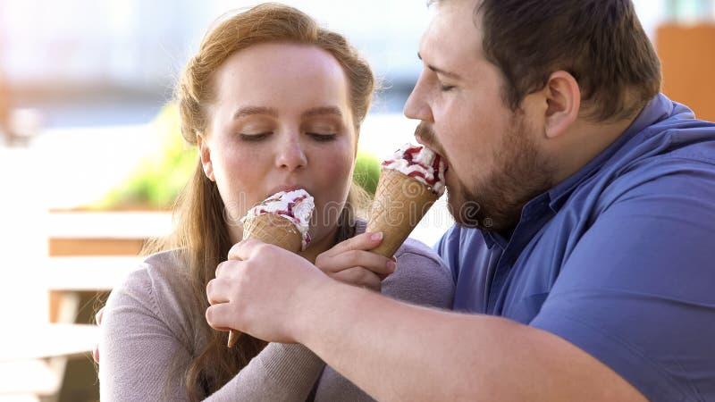 Zwaarlijvig houdend van paar die roomijs, suikerachtig zoet dessert delen, die op datum flirten stock afbeelding