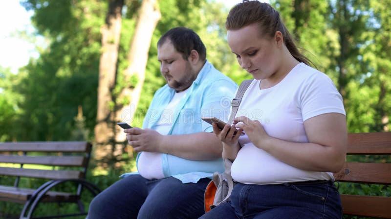 Zwaarlijvig jong paar die in sociale netwerken tijdens datum babbelen, schuw en onzeker stock afbeelding