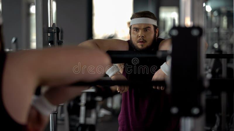 Zwaarlijvig mannetje uitgeput na trainingen in gymnastiek, die zijn gedachtengang in spiegel bekijken royalty-vrije stock foto's