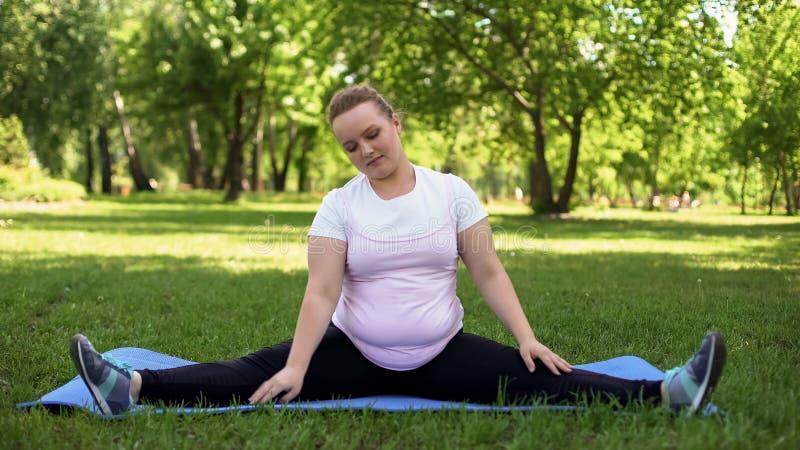 Zwaarlijvig meisje die spleten, geschiktheidsoefeningen doen in openlucht, manier aan gezonde levensstijl stock afbeeldingen