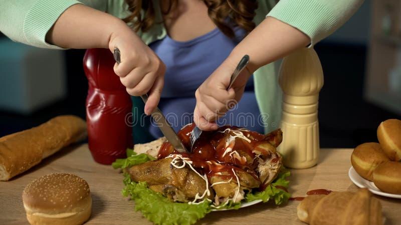 Zwaarlijvig tienermeisje die vettige die kip snijden met ketchup en mayonaise wordt behandeld royalty-vrije stock foto