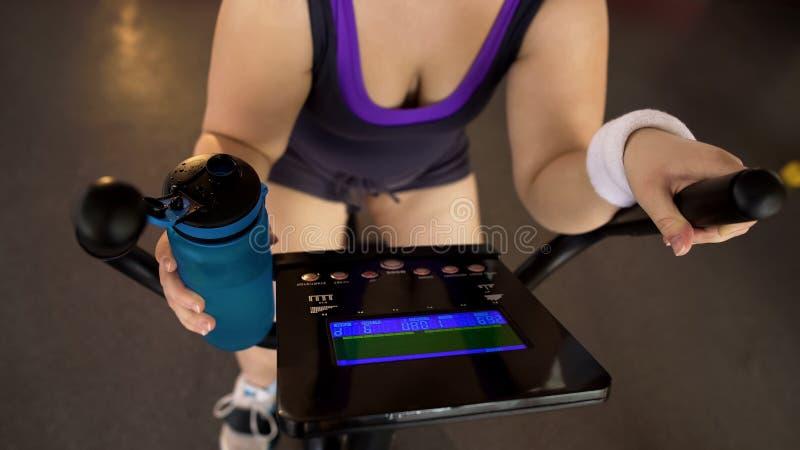 Zwaarlijvig vrouwen berijdend hometrainer en drinkwater, geschiktheid en gezondheidszorg stock fotografie