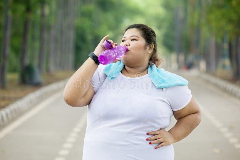 Zwaarlijvig vrouwen drinkwater na het doen van een training royalty-vrije stock afbeelding
