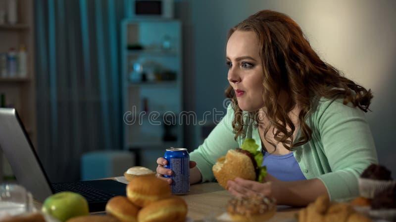 Zwaarlijvige dame die ongezond voedsel eten en op video's op laptop letten, luie levensstijl stock afbeelding