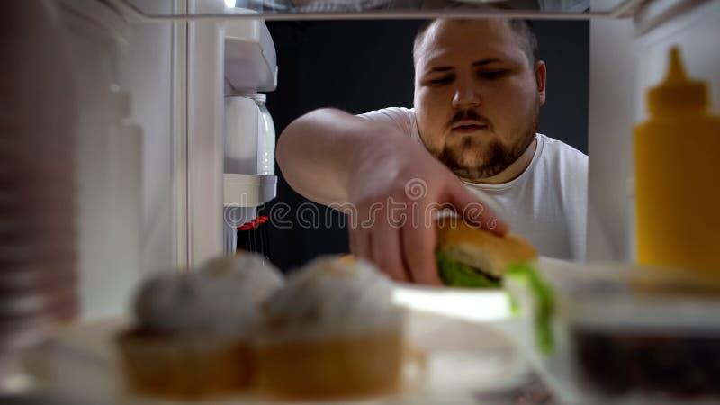 Zwaarlijvige hongerige mens die hamburger van koelkast, dieetmislukking, ongezonde levensstijl nemen stock foto's