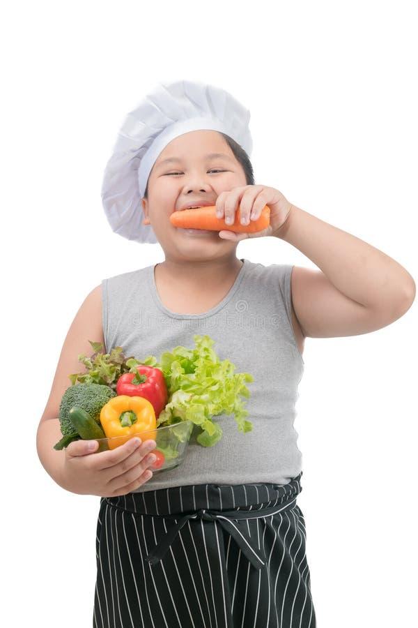 Zwaarlijvige jongenschef-kok die geïsoleerde wortel eten royalty-vrije stock afbeeldingen