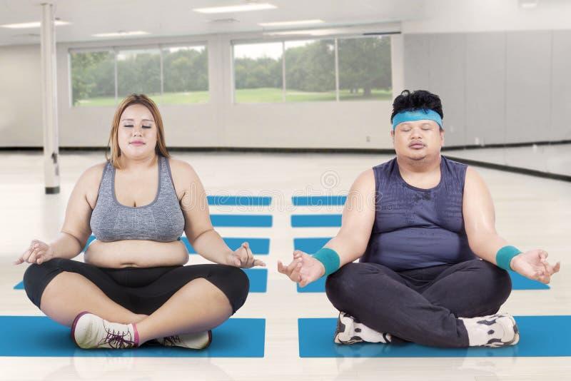Zwaarlijvige mensen die in de klassenyoga mediteren royalty-vrije stock foto