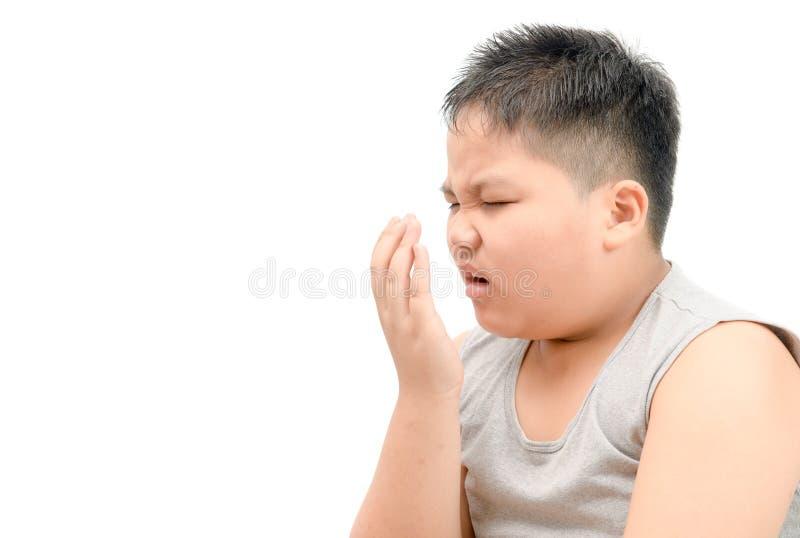 Zwaarlijvige vette jongen die zijn geïsoleerde adem met zijn hand controleren stock afbeeldingen