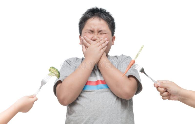 Zwaarlijvige vette jongen met uitdrukking van afschuw tegen groenten royalty-vrije stock afbeeldingen