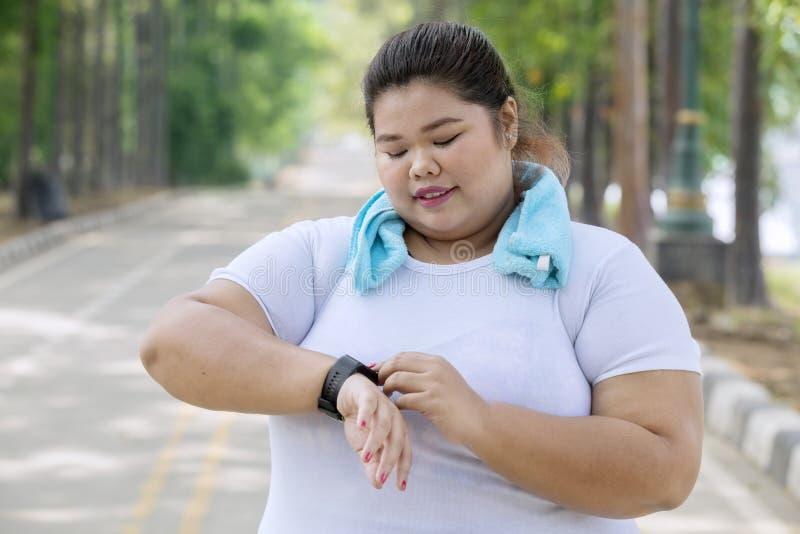 Zwaarlijvige vrouw die haar smartwatch op de weg dragen royalty-vrije stock fotografie