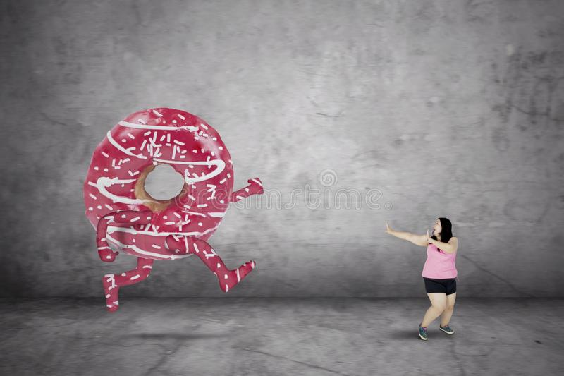 Zwaarlijvige vrouw die vanaf een doughnut lopen stock foto's