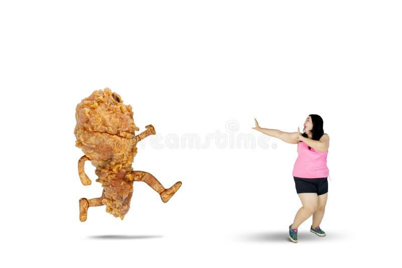 Zwaarlijvige vrouw die vanaf een gebraden kip lopen stock fotografie