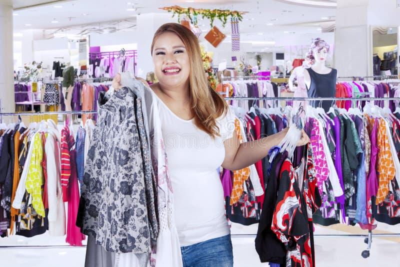 Zwaarlijvige vrouw die veel kleding in de boutique dragen royalty-vrije stock afbeeldingen