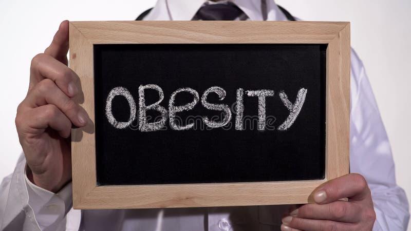 Zwaarlijvigheid op bord in artsenhanden wordt geschreven, gezonde voedingsaanbevelingen die stock fotografie