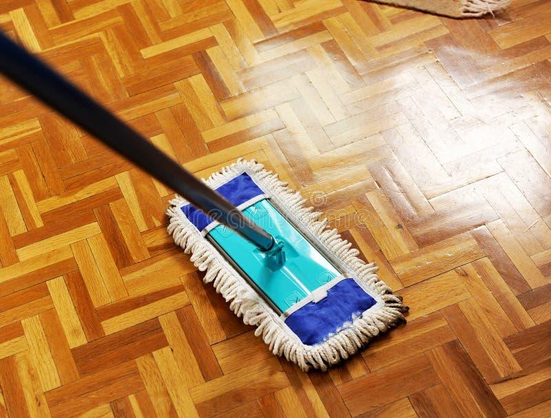 Zwabber die houten vloer wassen stock foto