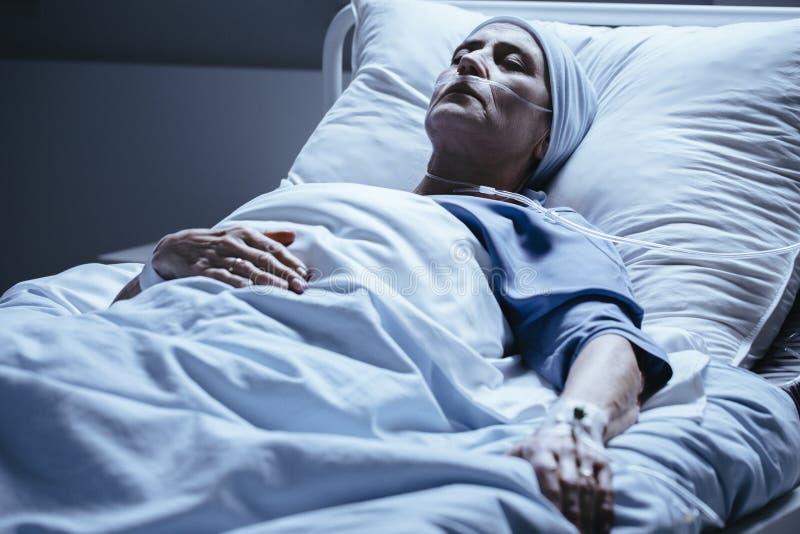 Zwakke hogere vrouw met kanker tijdens behandeling in het ziekenhuis royalty-vrije stock afbeeldingen