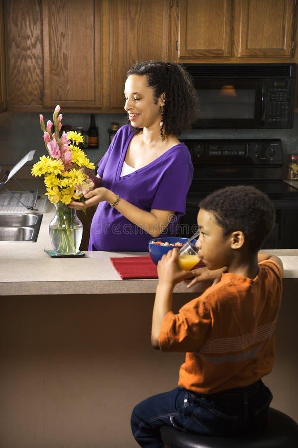 Zwanger mamma dat bloemen schikt royalty-vrije stock fotografie