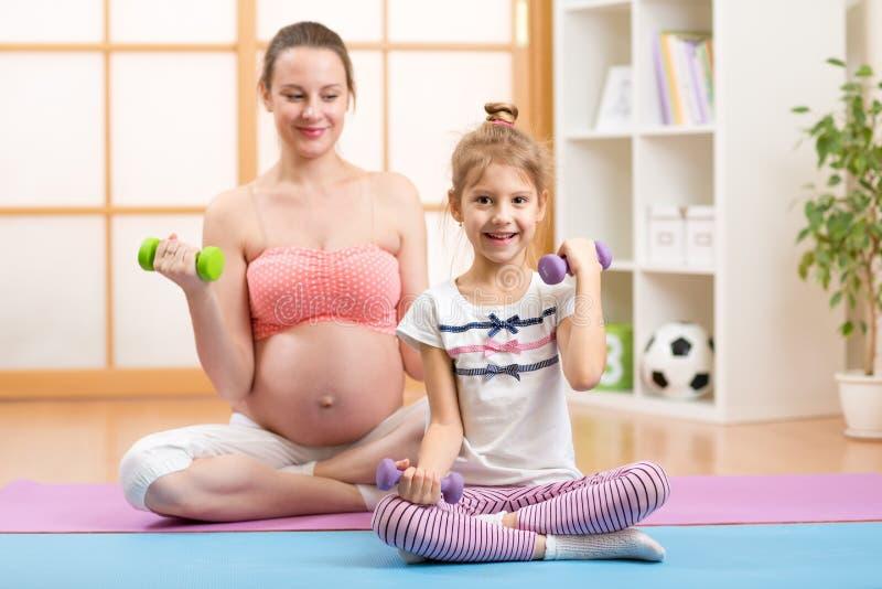 Zwanger mamma en ouder kind die geschiktheid doen met stock afbeelding