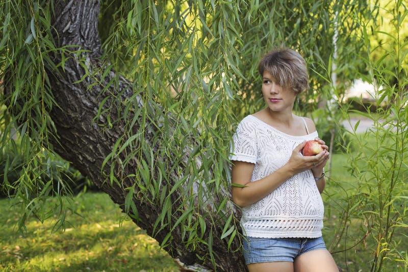 Zwanger meisje die een appel eten royalty-vrije stock foto