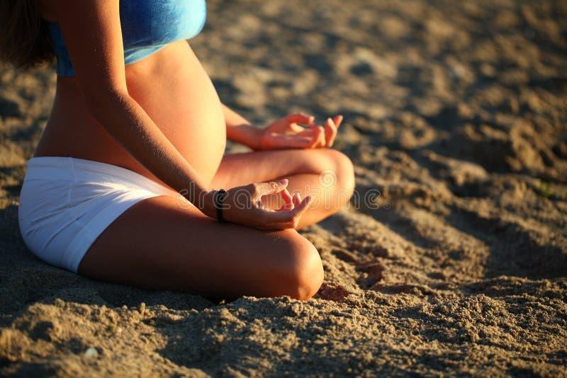 Zwanger meisje die het strand overzeese van het yogazand ochtend doen stock foto