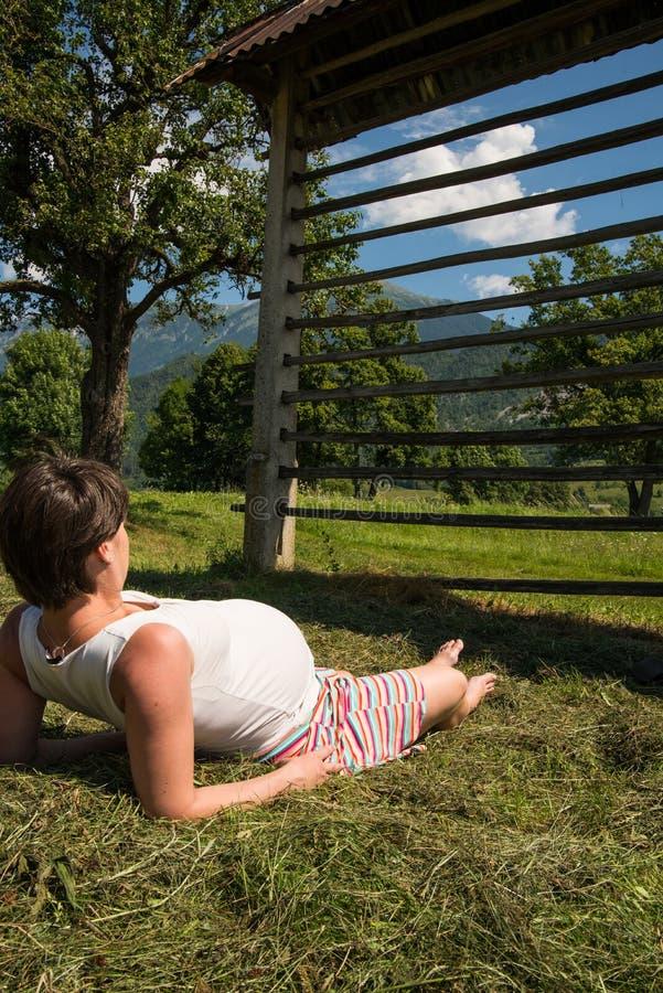 Zwanger meisje die op gras rusten stock afbeeldingen
