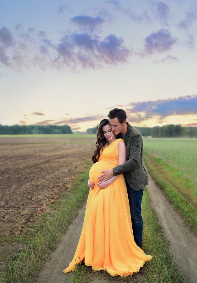 Zwanger meisje met een jonge mensenomhelzing die, zich naast het gebied bij zonsondergang bevinden stock afbeeldingen