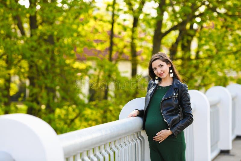 Zwanger meisje op de brug Portret van een jonge gelukkige zwangere vrouw op een witte brug De rust en geniet van aard stock foto's