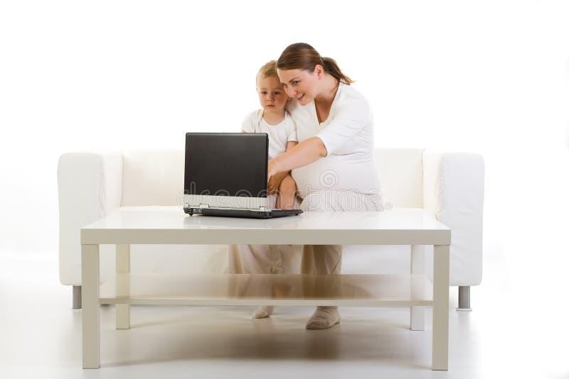 Zwanger moeder en kind die PC met behulp van royalty-vrije stock fotografie