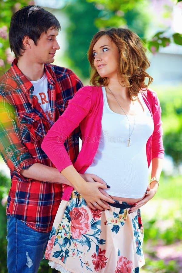 Zwanger paar in bloeiende de lentetuin stock foto