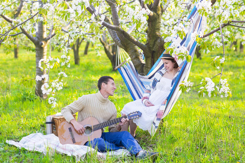 Zwanger paar in bloeiende tuin bij de picknick royalty-vrije stock fotografie